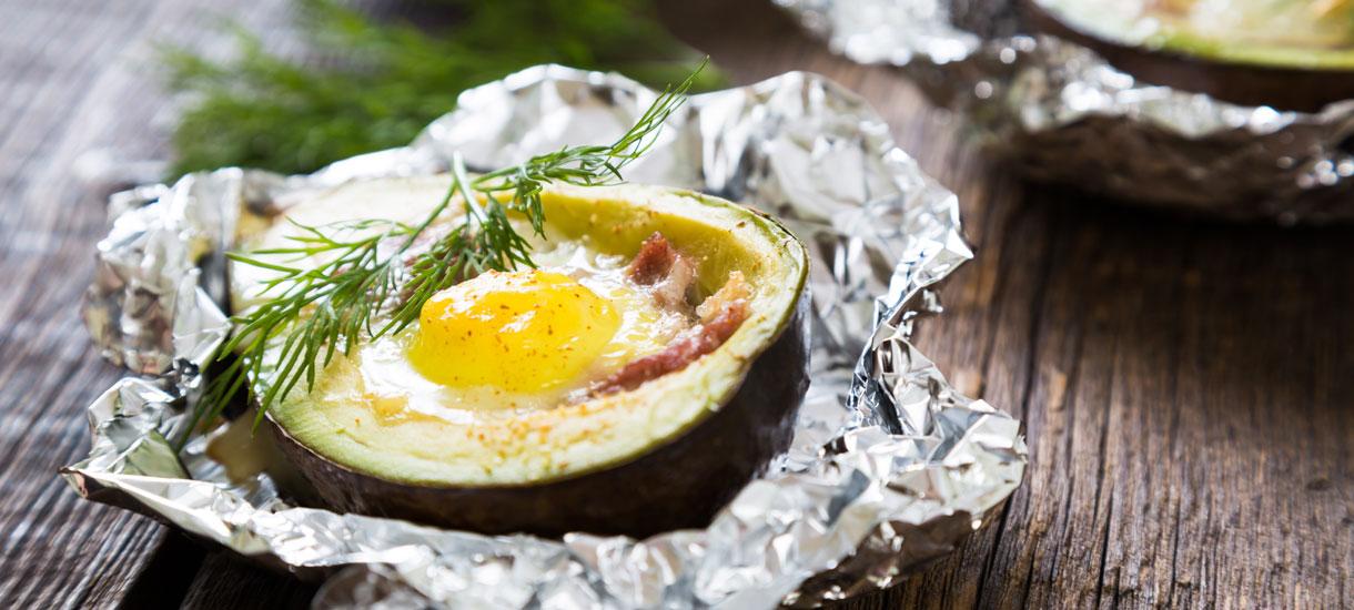 Gegrilde avocado met ei en spek van de barbecue