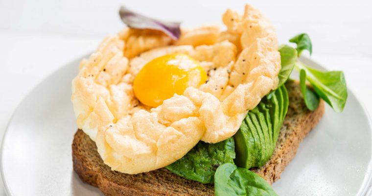 Cloud eggs met avocado en veldsla op geroosterd brood