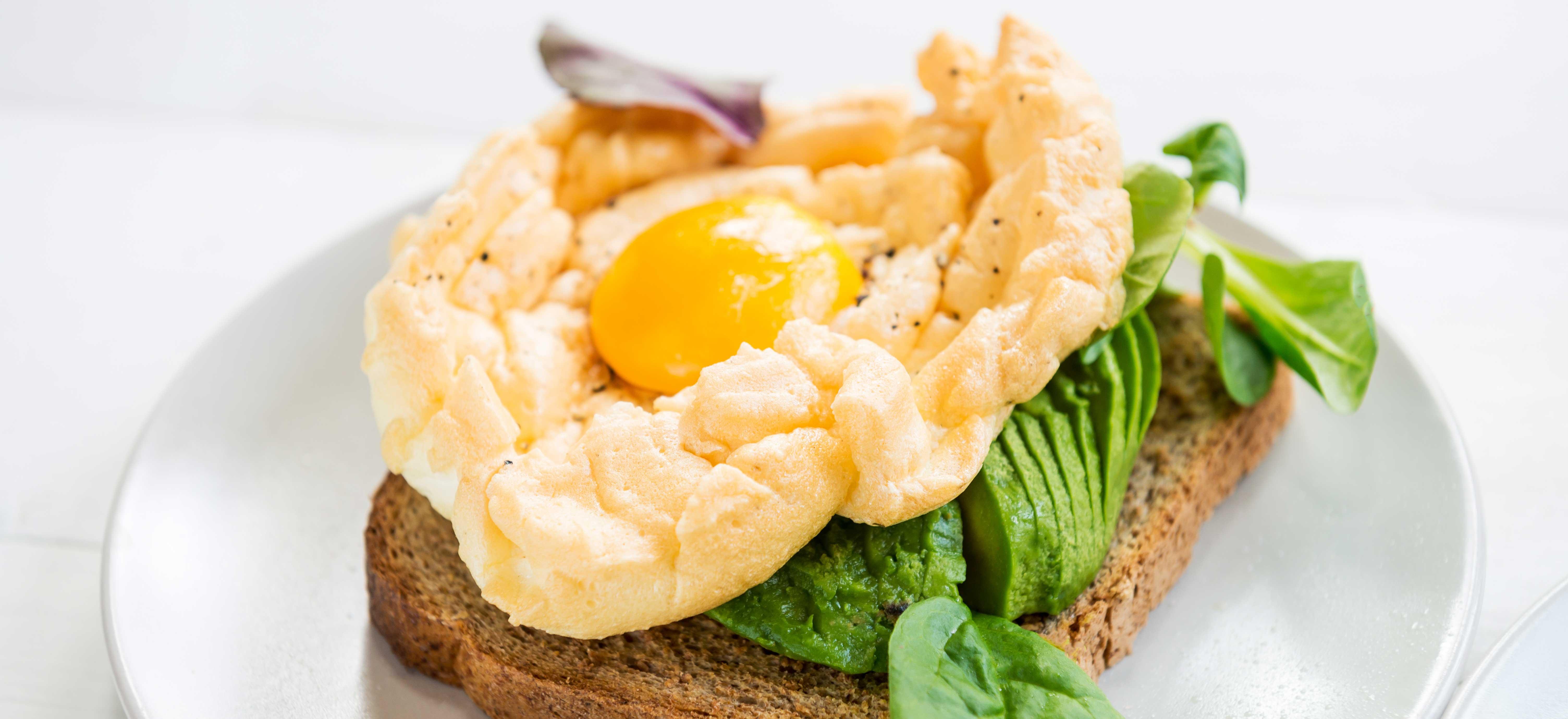 Cloud eggs met avocado en veldsla op geroosterd brood